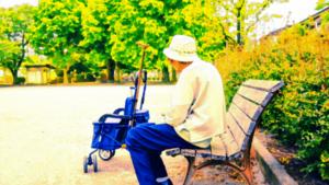 認知症のおじいさんが外のベンチに座っている