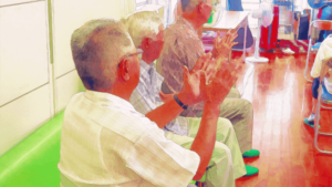 デイサービスの利用者が椅子に座り拍手をしている